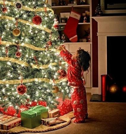 девочка вешает шарик на елку