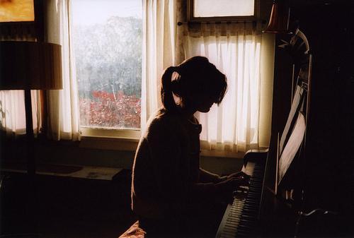 девочка в окне играет на пианино