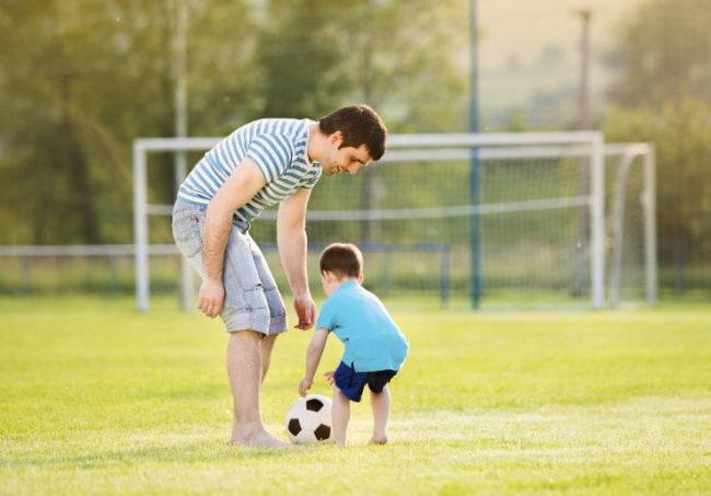 папа играет с сыном в футбол